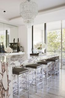 Create a statement by adding an oversized chandelier to polished marble counters and wooden floorboards.