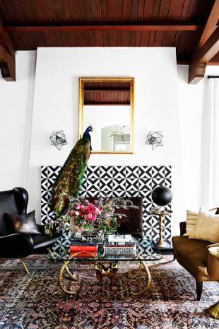 A living room glammed up with black and white tiles, ceiling beams, a gold mirror, and a peacock.