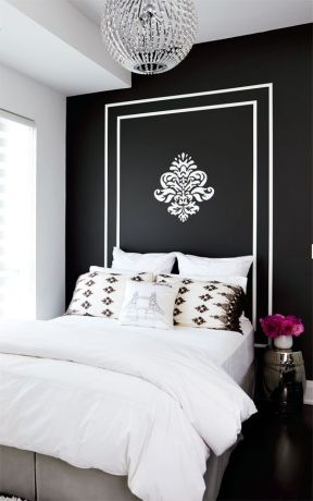 Crisp white bedding adds a modern contrast to dark walls in this bedroom.