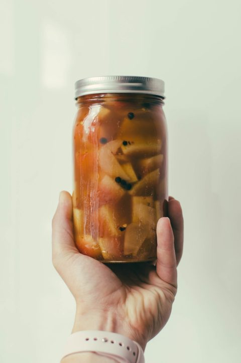 Watermelon rind pickling in a jar held up by hand - The Mummy