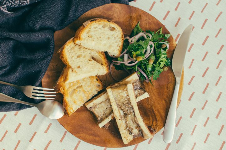 Top view, two pieces of bone marrow and toast on a wood plate against a fabric background - The Mummy