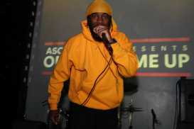 Dougie F performing in his signature yellow do-rag