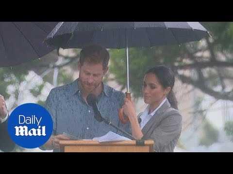 Meghan holds an umbrella for Harry as he speaks in Dubbo