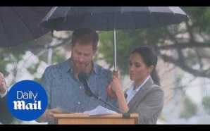Meghan holds an umbrella for Harry as he speaks in…