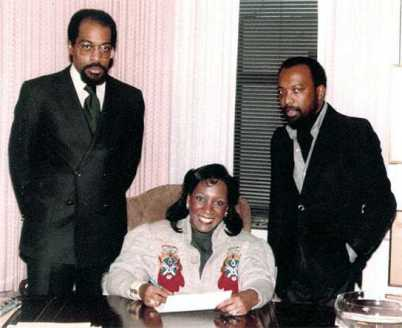Signing a recording contract in the 1980s.