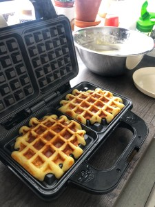 Waffles being cooked in a waffle iron.