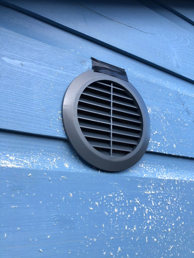 Circular vent installed on exterior of shed.