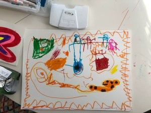 Stick figure scene on art table with supplies.