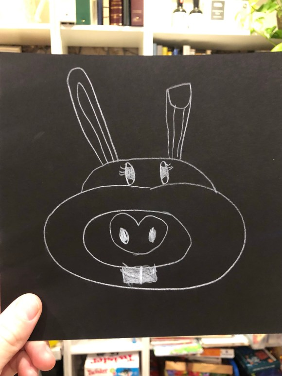Sketch of a bunny in white pencil on black paper.
