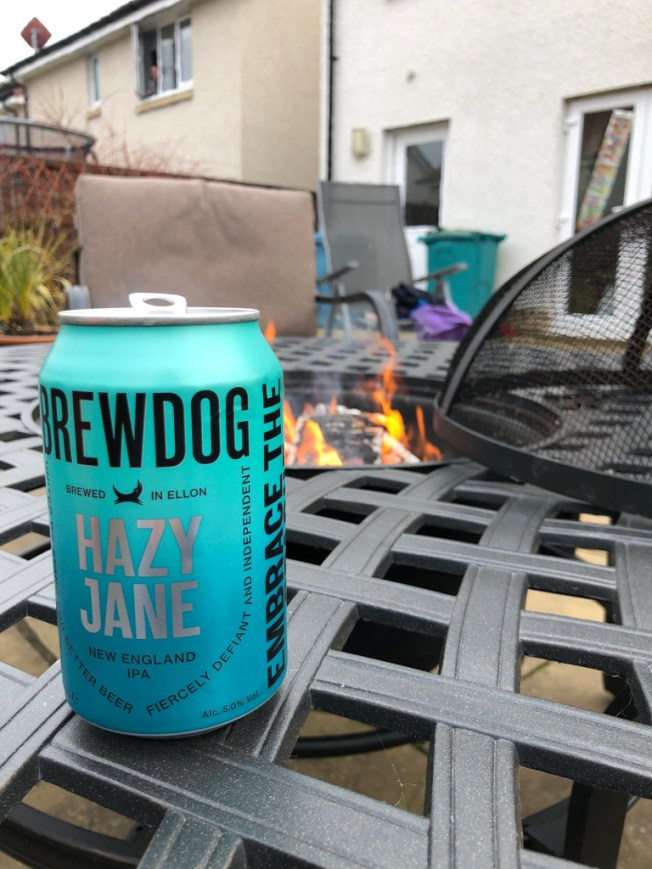 Beer car on a table in front of a fire pit.