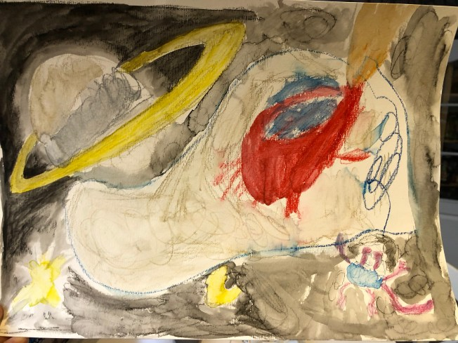 Kids painting of a planet and rocketship.
