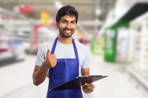 Indian male worker at hypermarket or supermarket showing thumb-up like gesture while holding clipboard