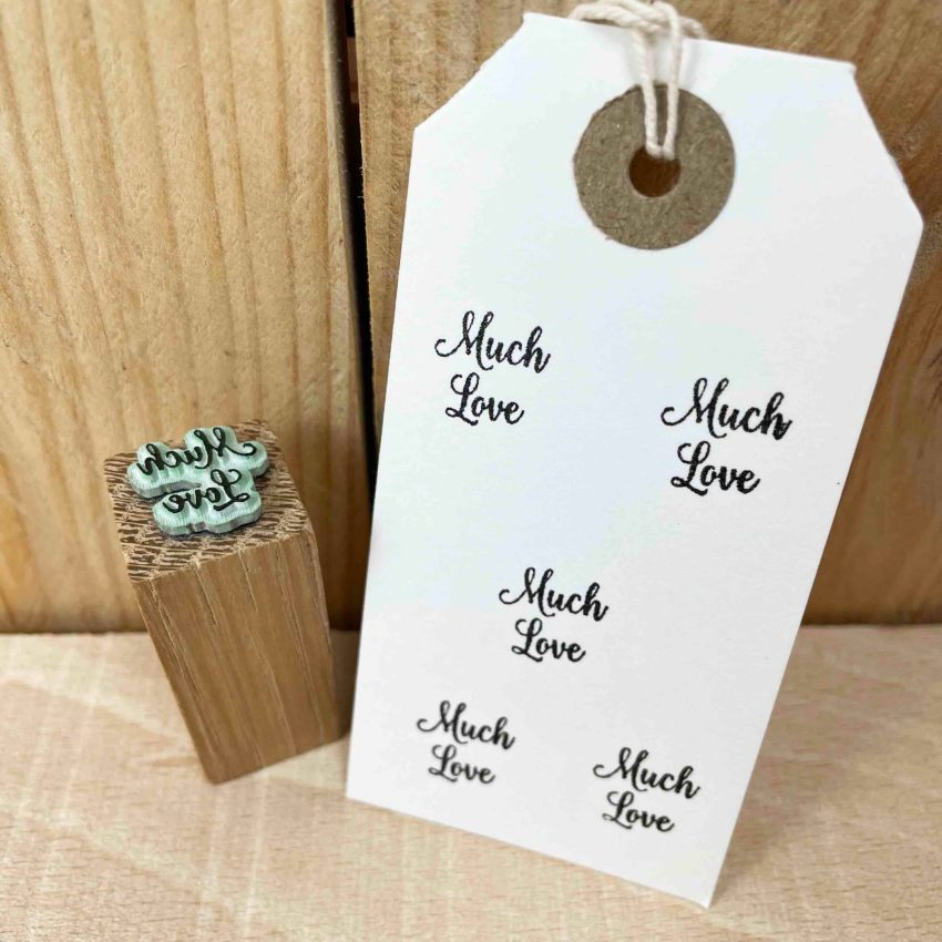 small rubber stamp that reads 'much love' in cursive script