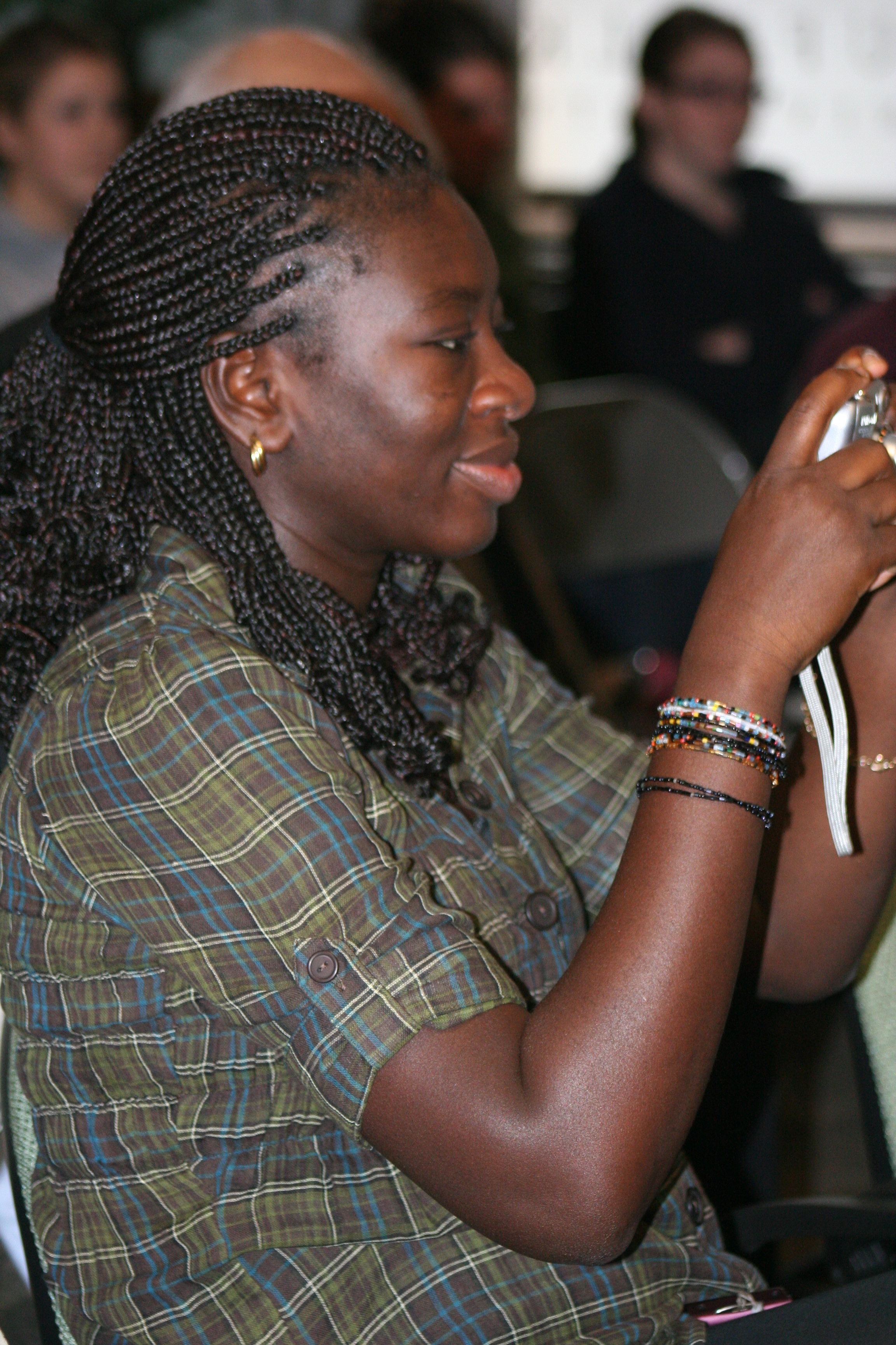 Ndeye Ngom Faye takes a picture of her husband giving his presentation.