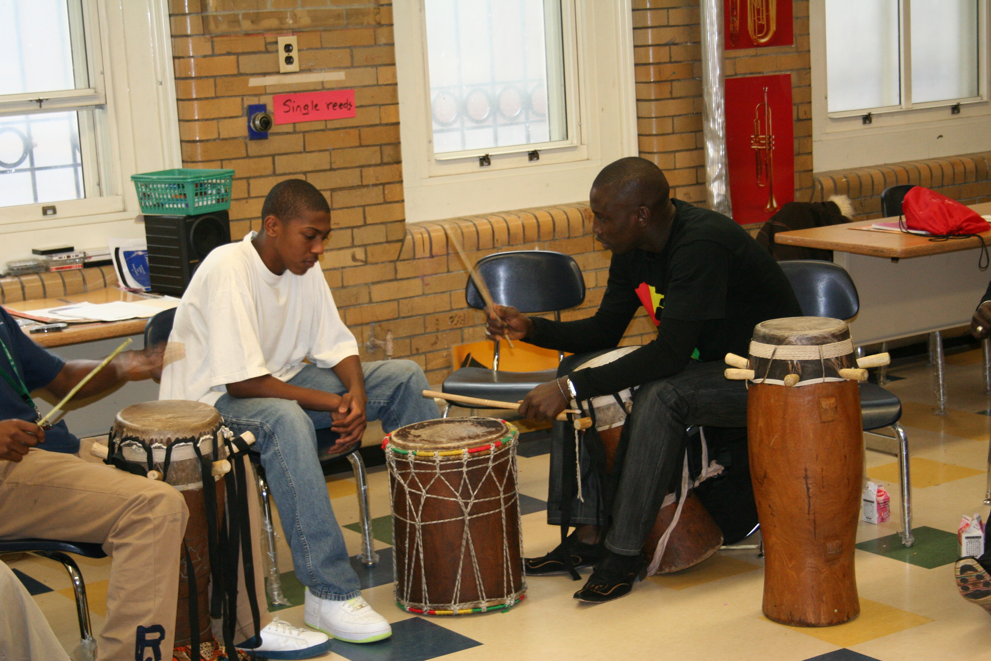 Aziz works with a student on drum technique.