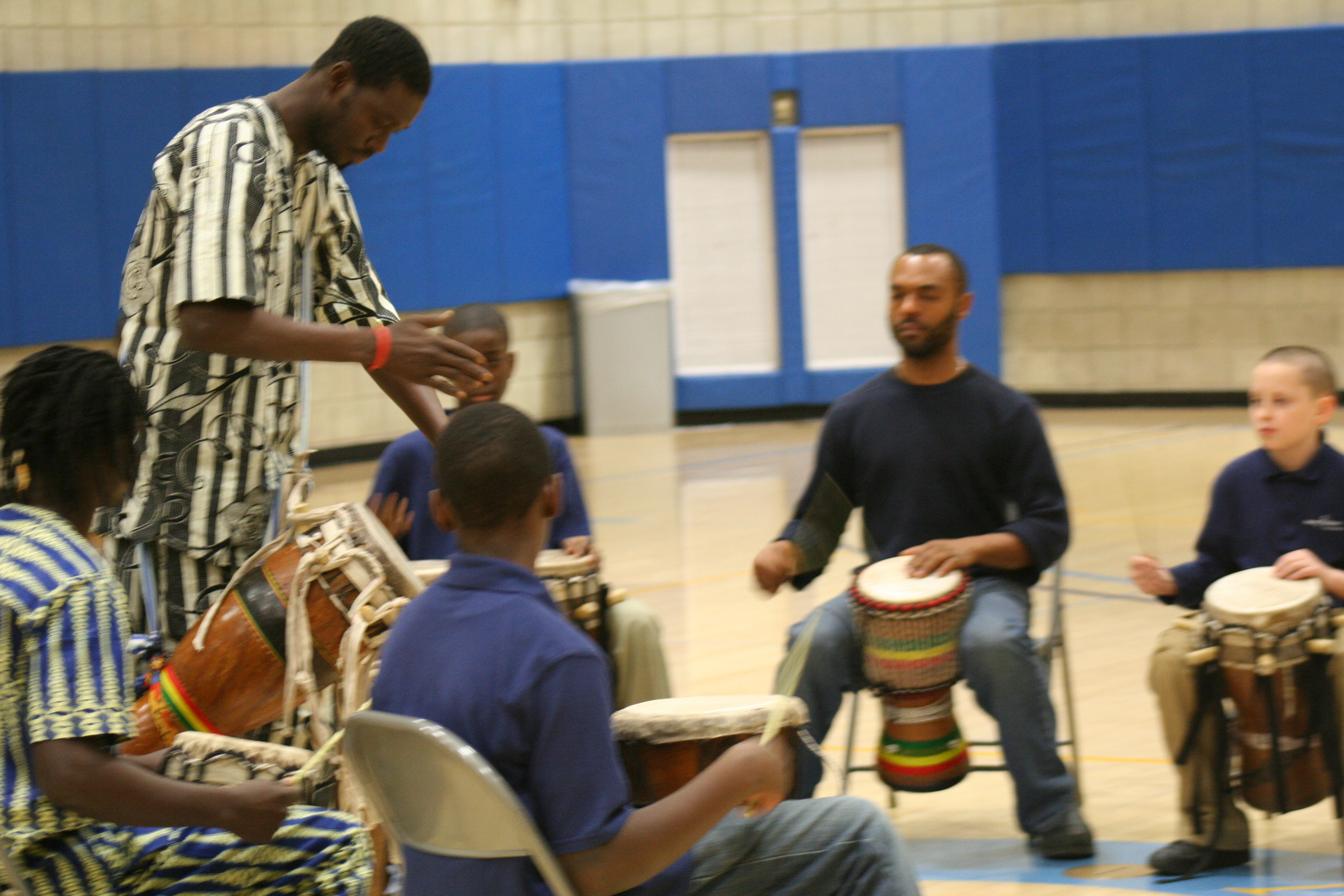 Moustapha leads the Young Achiever School students in a rhythm.