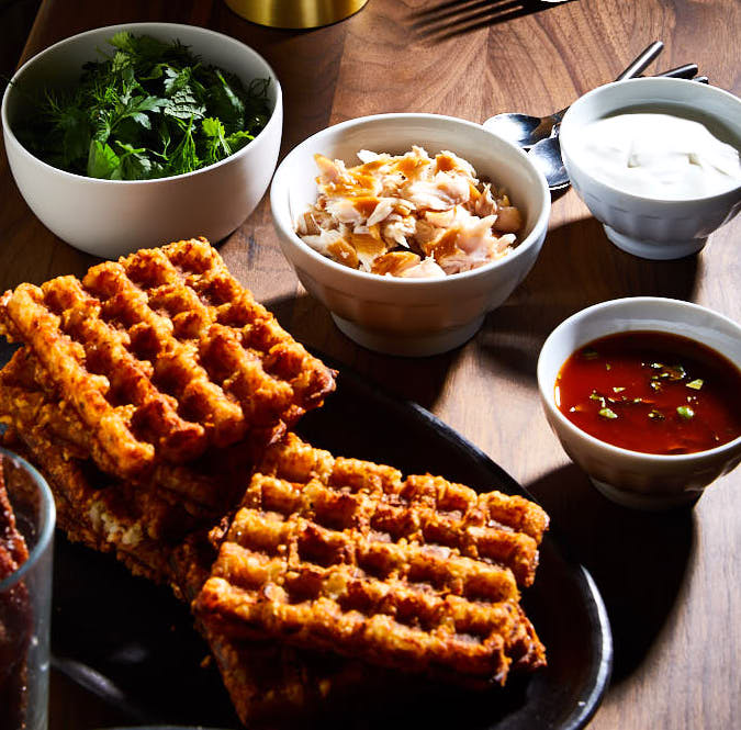 Tater Tot Waffles with Smoked Trout, Sour Cream, Chermoula, and Herb Salad