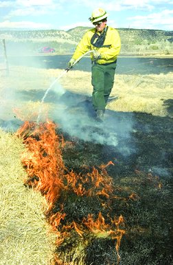 Cpt. Jim Owens with Los Pinos Fire Protection District tends to a fire along County Road 213 on Tuesday.
