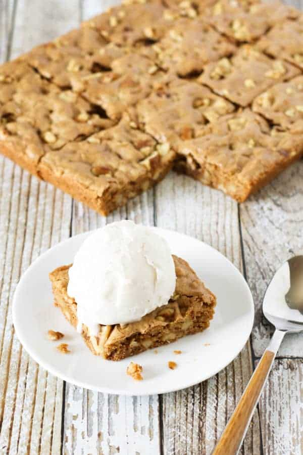 walnut blondies in the background with a blondie on a plate topped with whipped cream in the foreground