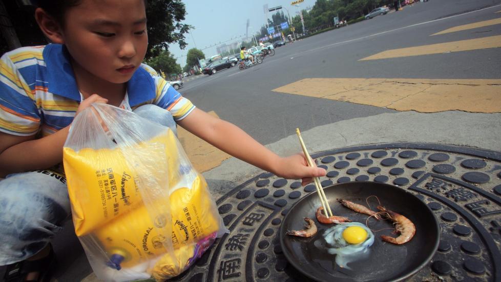 STEKER EGG: Gutten steker egg og reker på et kumlokk i Jinan i det som er den verste hetebølgen i Kina på 140 år.. Bildet er fra i går. Foto: EPA / ZHENG TAO CHINA / NTB scanpix