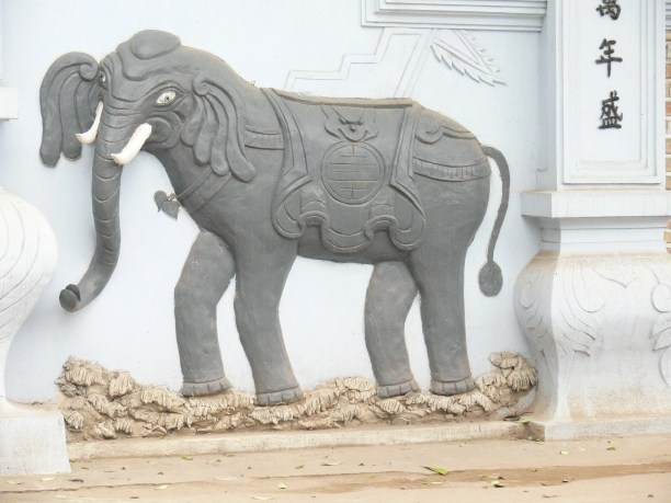 Elephant on wall with double happiness - outside a temple on North shores of West Lake.
