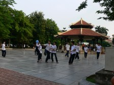 Vietnamese school boys play football on the tiled area behind Ly Thai To statue, Ly Thai To Park, Hanoi, Vietnam.
