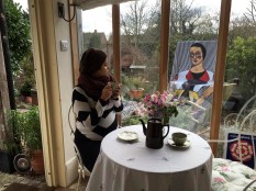 Jana enjoys tea while Eve does the gardening.