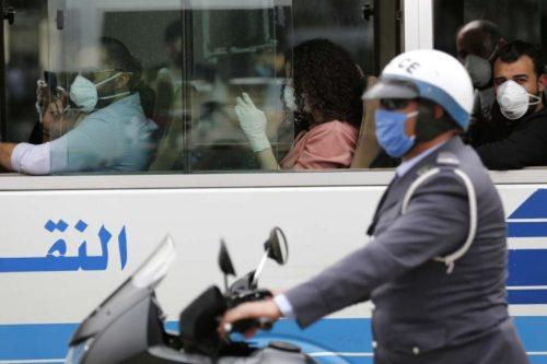 شرطي سير بجانب باص يحمل مسافرين بعد وصولهم إلى مطار رفيق الحريري في بيروت، لبنان (أ ب)