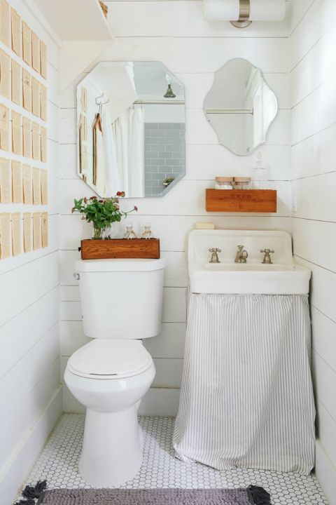 In a tiny guesthouse, even the bitty bathroom doesn't feel cramped thanks to white-washed siding. A set of mismatched mirrors doubles down on charm.