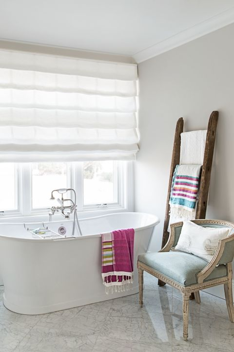 Instead of hiding your prettiest linens in a closet, put them on display via a wooden ladder. In an airy beach house, the upgraded towel bar stands within reach of a freestanding tub.