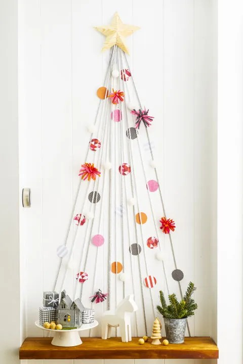 "Use yarn to style a mini version on an empty wall or in a hallway. Enlist the kids to dress it to the nines with paper-circle ""ornaments"" and felt, attached with tape."