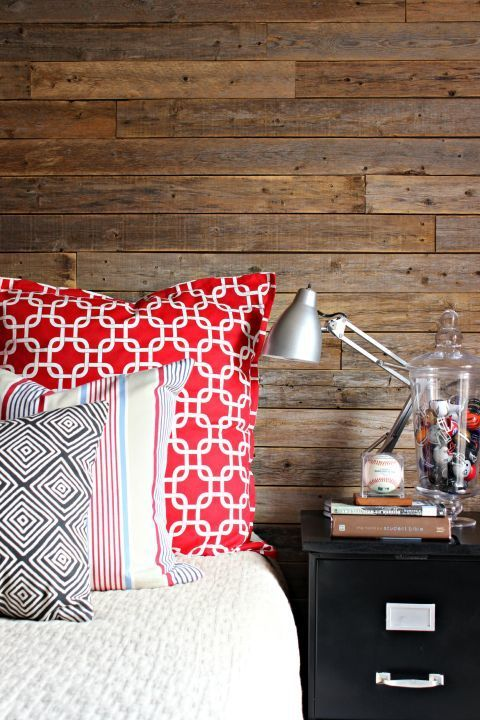 Skip the pros and DIY your own plank wall like in this bedroom. Paired with bold linens, the rustic wood feels fresh, not quaint.