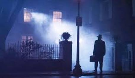 Movie Still from The Exorcist. The exorcist standing in front of the house.