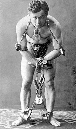 Harry Houdini, full-length portrait, standing, facing front, in chains https://en.wikipedia.org/wiki/Harry_Houdini#/media/File:HarryHoudini1899.jpg