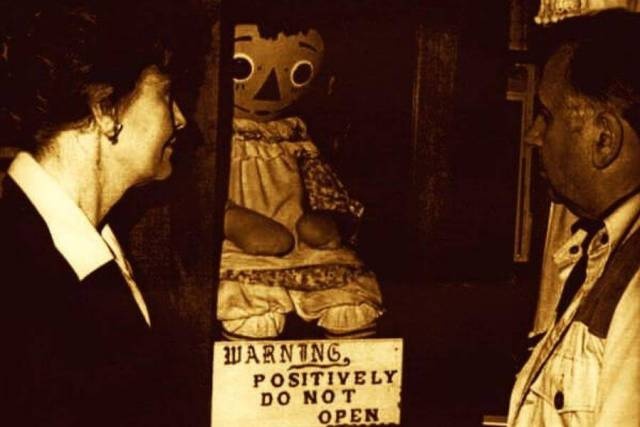 Warrens' Occult MuseumEd and Lorainne Warren look upon the original Annabelle doll in her glass case.