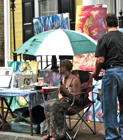 Artist Crystal A. Frascatore shelters under an umbrella during morning drizzle