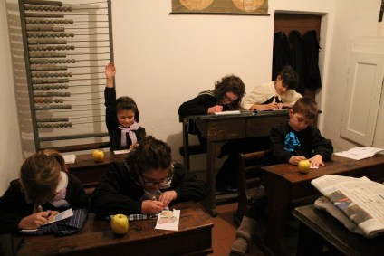"SCUOLA/SCHOOL: Local kids act as pupils in a very small ""shcořa"", Kye for school, in which an old abacus and planisphere can be observed. (Performers: Maria Capra, Sofia Maule, Francesca Luciano, Beatrice Luciano, Gloria Anfossi, Lorenzo Sevega) (Gianluca Avagnina Photography)"