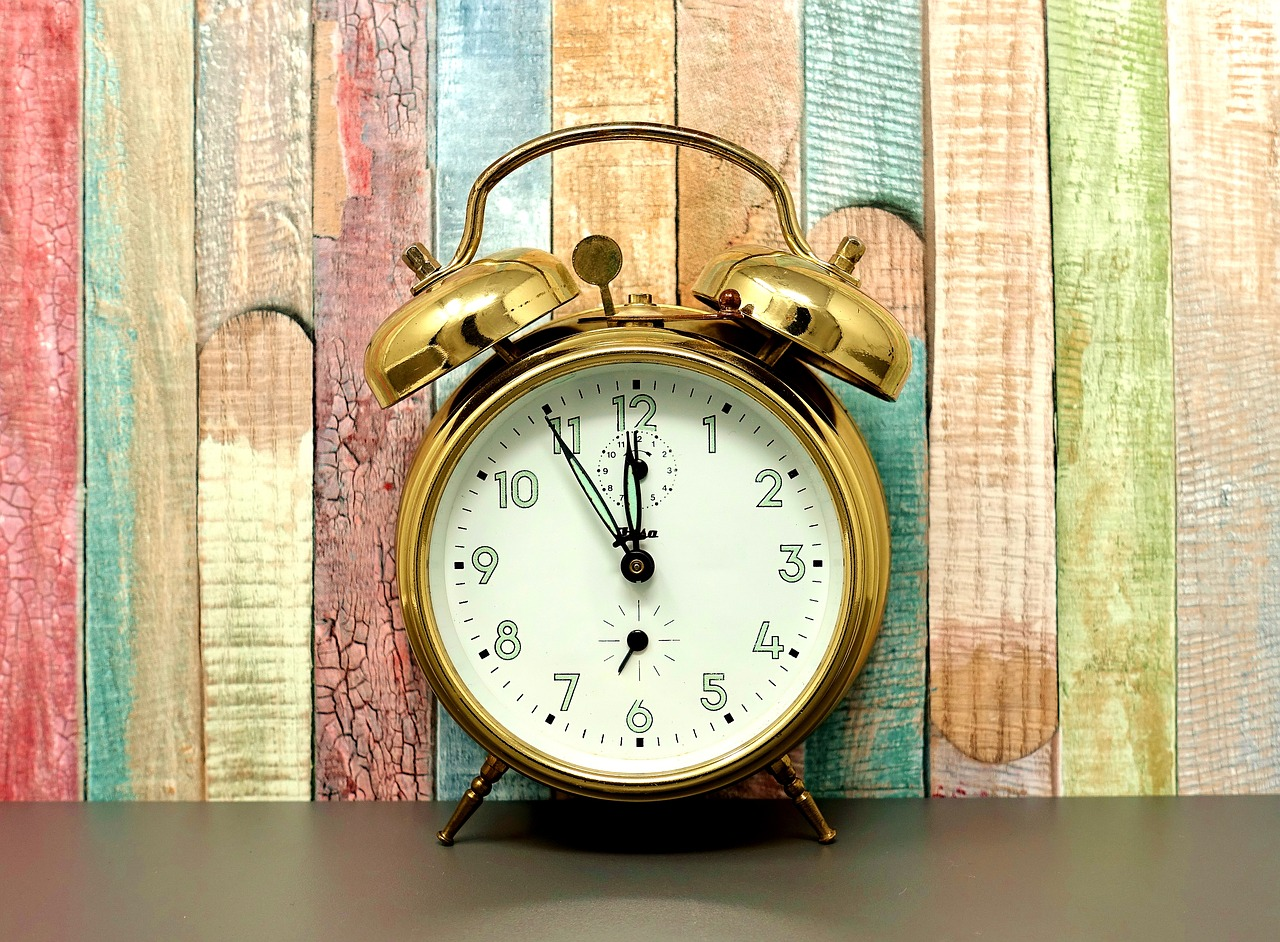 Gold alarm clock against wood wall