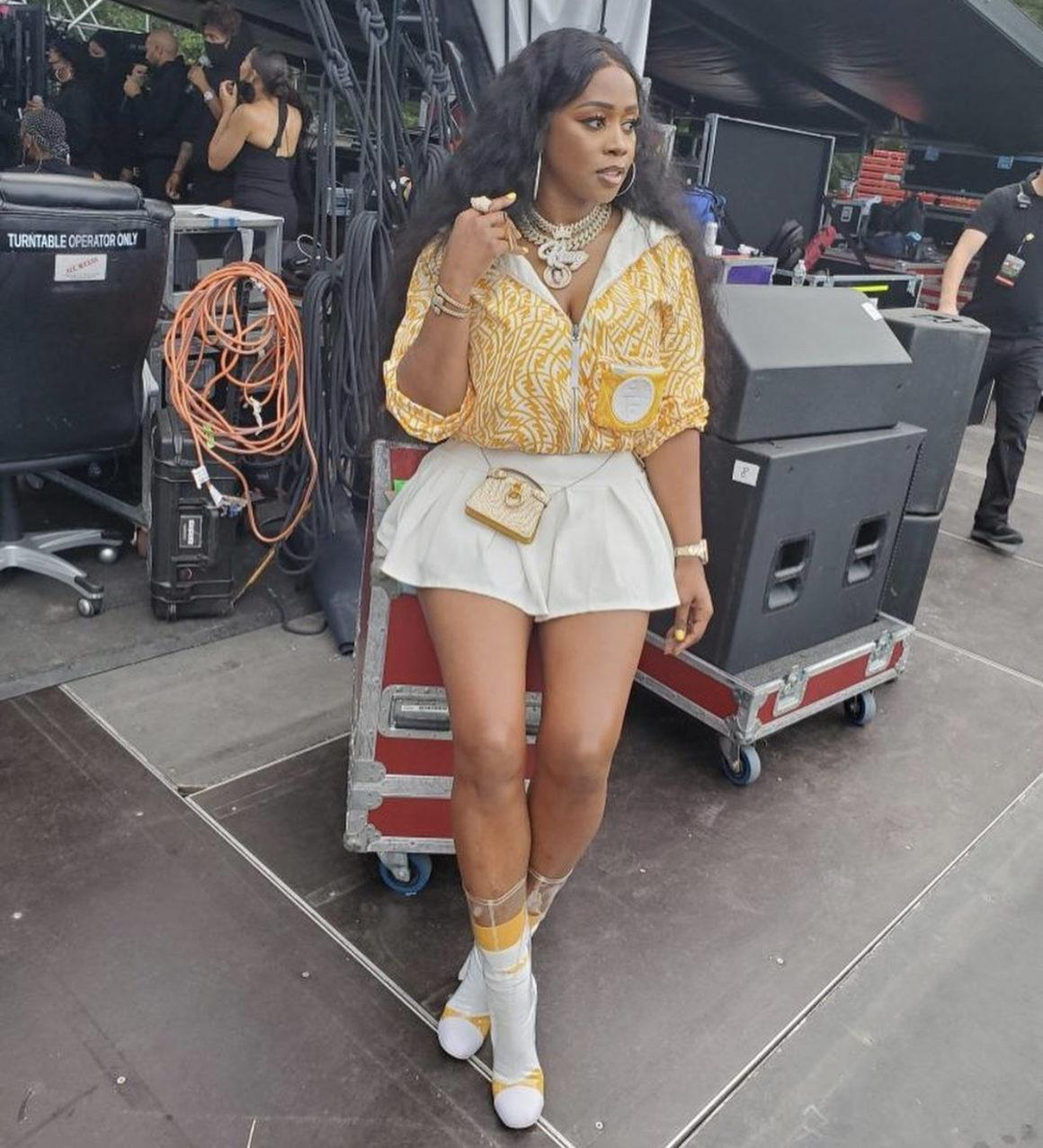 Remy Ma Performs at 'We Love NYC' Concert Wearing Fendi Yellow and White Logo Jacket, Purse, and Socks Paired With Ms. Bling Pleated White Mini Skirt and Chanel PVC Boots