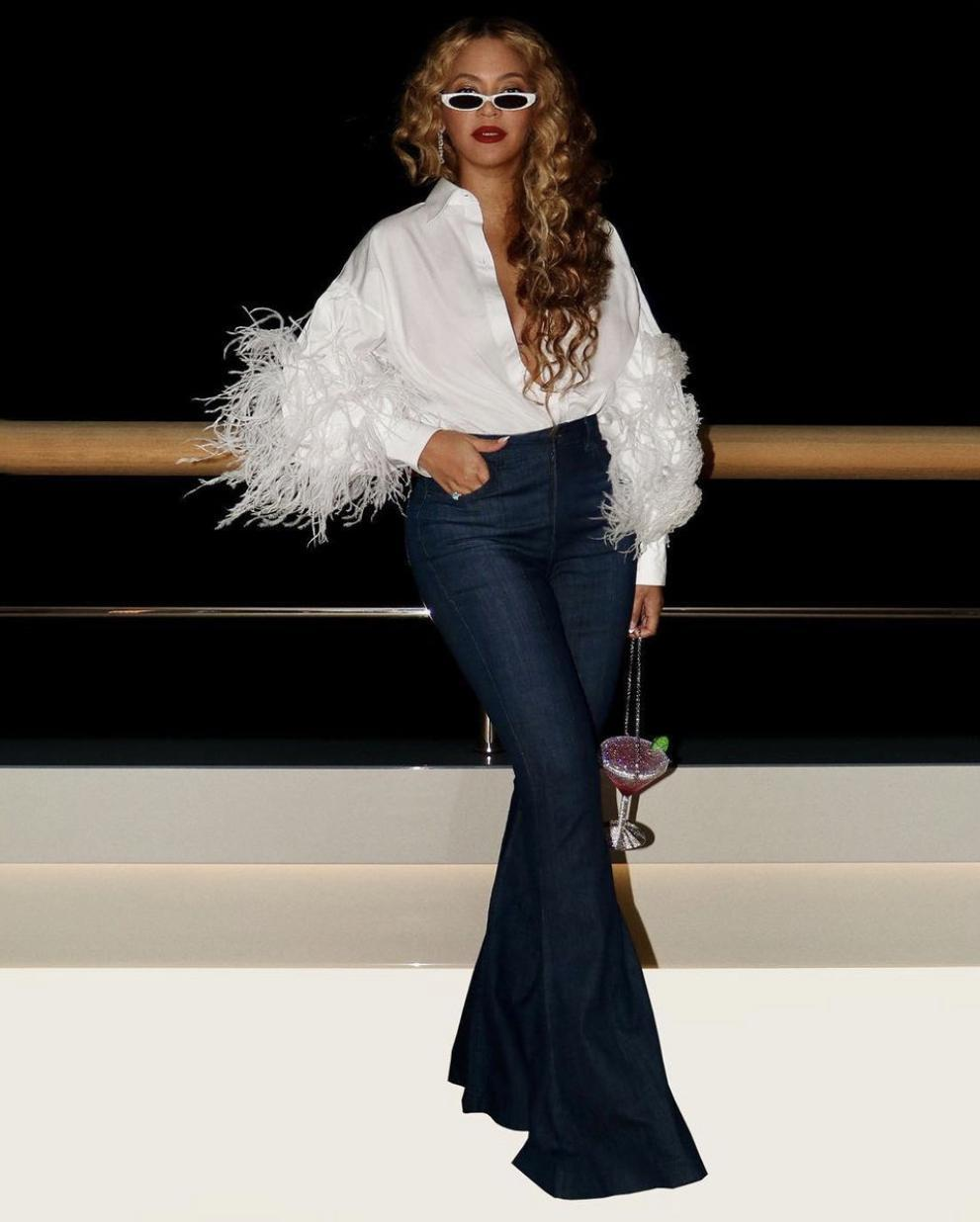 Beyoncé Spotted Yachting in Capri With Jay-Z Wearing Valentino White Feather Shirt, Flare Leg Jeans, PHILÓ White Sunglasses, and Judith Leiber Martini Clutch