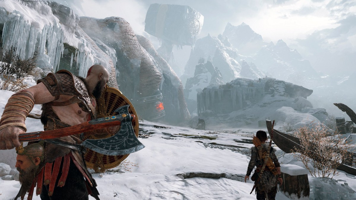 Kratos and Atreus apporavh a massive fallen statues in a snowy tundra.