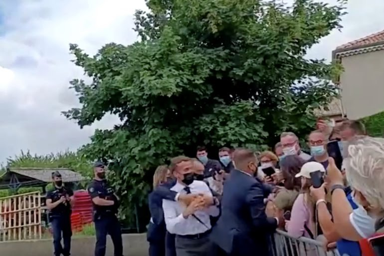 French President Emmanuel Macron is protected by security guards after being slapped by a member of the public [BFM TV/Reuters]