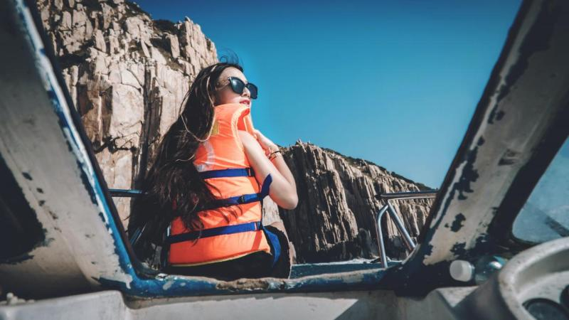 woman with life vest sitting on boat facing brown mountain