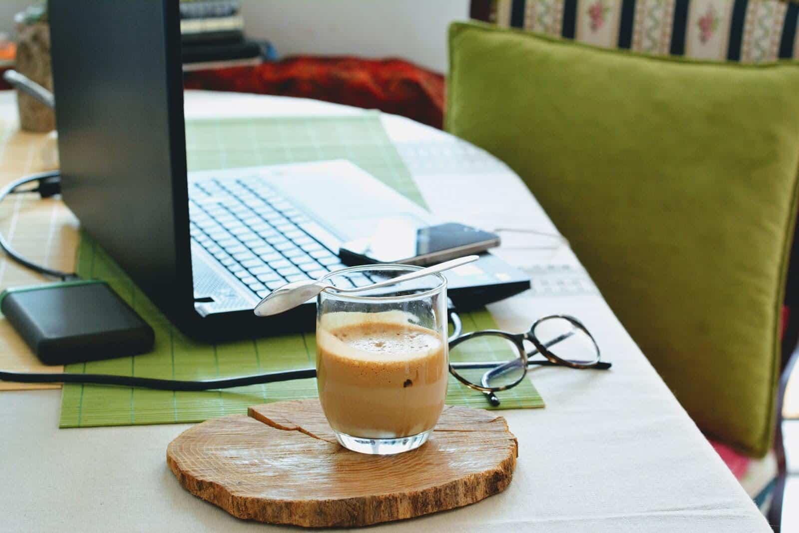 Legitimate work at home jobs: Setup of laptop, phone, coffee, and eyeglasses