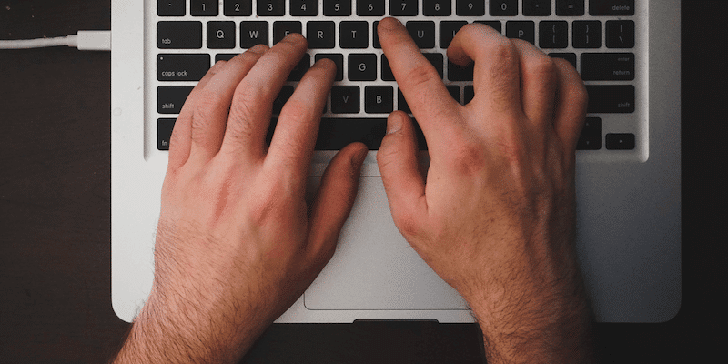 Hands typing on MacBook keyboard for gig economy job
