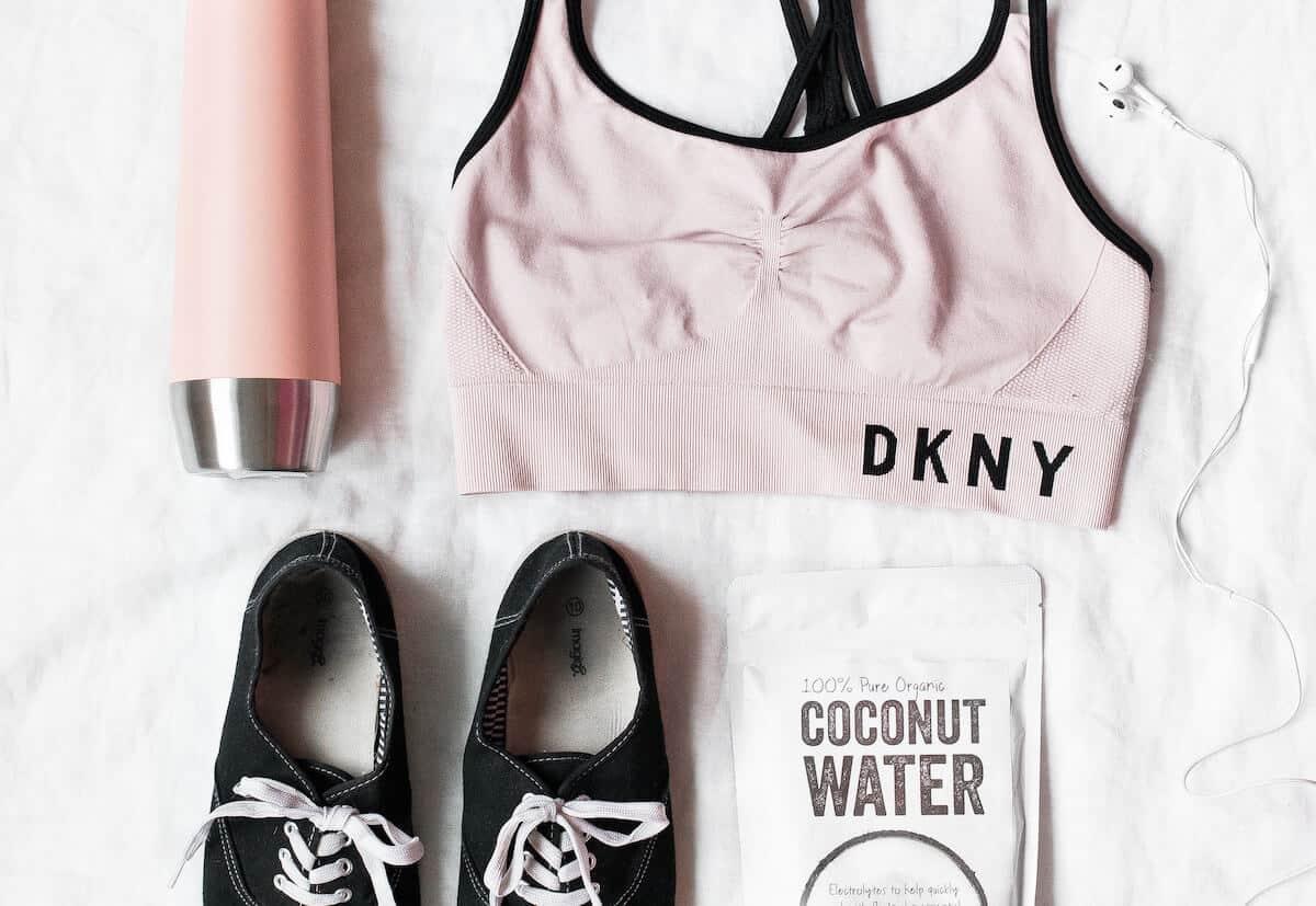 Flatlay of sports bra, water bottle, tennis shoes, coconut water