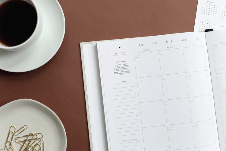 Desk with a calendar, cup of coffee, and paper clips