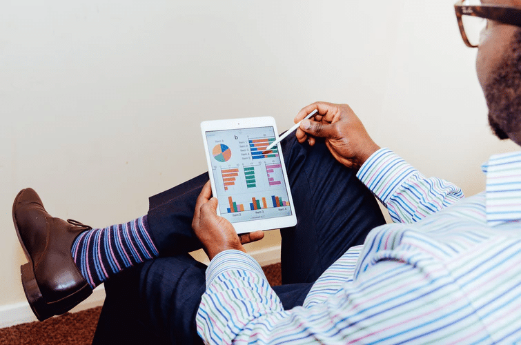 Opinion Outpost: A well-dressed man looks at charts on a tablet
