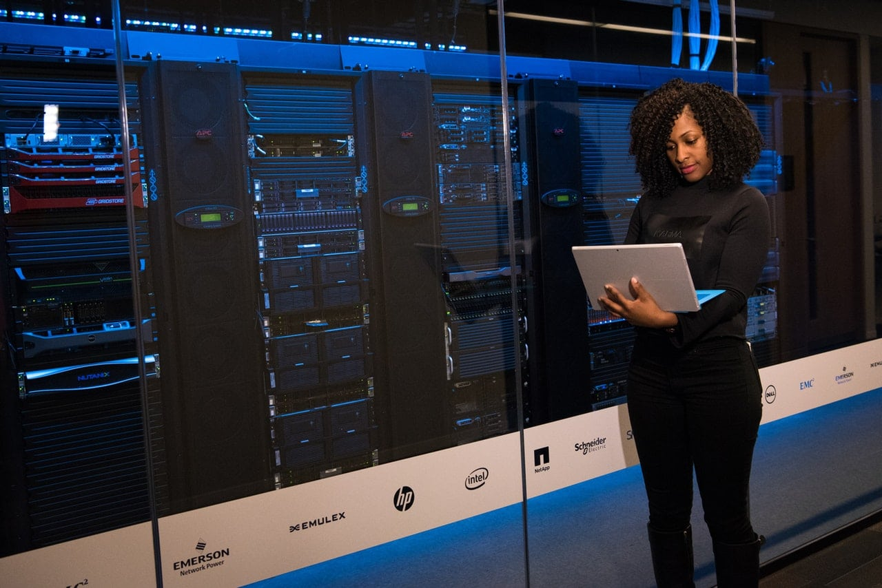 Woman holding a laptop while standing in a data center