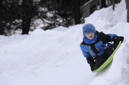 kid on sled on banked curve